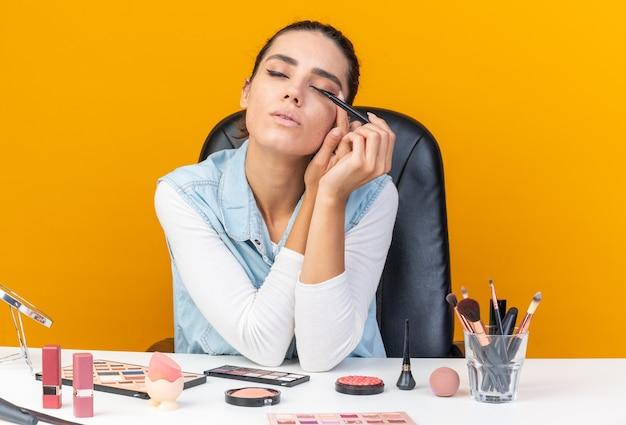Selbstbewusste, hübsche kaukasische frau, die mit geschlossenen augen am tisch sitzt und make-up-tools aufträgt, die eyeliner auftragen