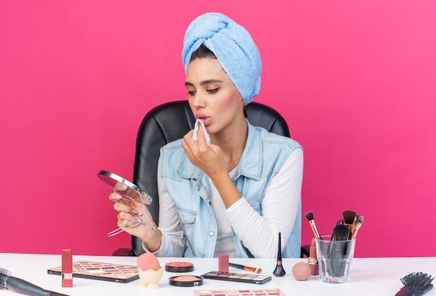 Selbstbewusste, hübsche kaukasische frau mit eingewickeltem haar in handtuch, die am tisch mit make-up-tools sitzt und den spiegel hält und sich den mund mit einer serviette abwischt