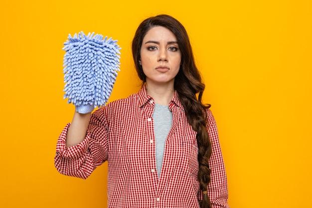Selbstbewusste hübsche kaukasische putzfrau, die mikrofaser-reinigungshandschuh hält und schaut