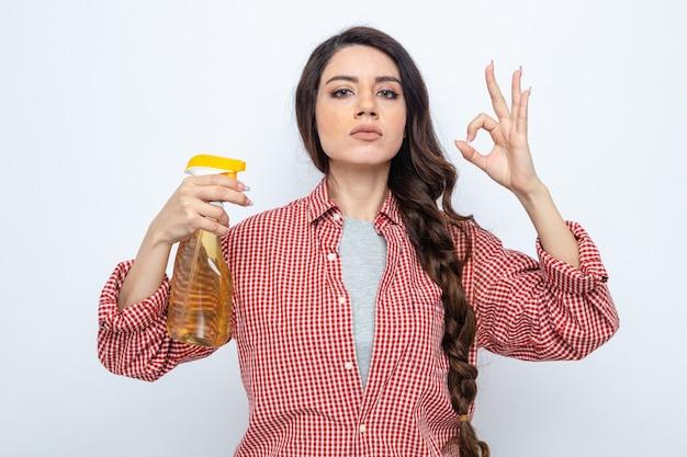Selbstbewusste hübsche kaukasische putzfrau, die sprühreiniger hält und ein ok-zeichen gestikuliert