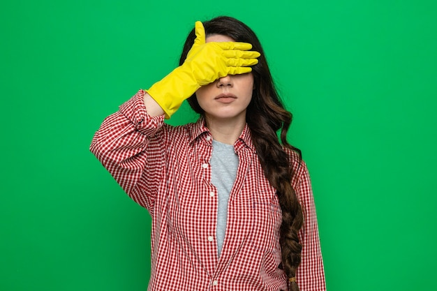 Selbstbewusste hübsche kaukasische putzfrau mit gummihandschuhen, die ihre augen mit der hand bedecken