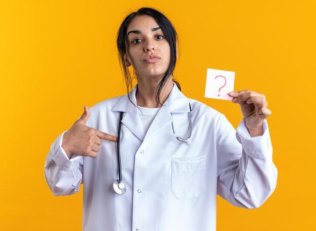 Selbstbewusste junge ärztin, die ein medizinisches gewand mit stethoskop hält und punkte auf fragezeichenpapier auf gelber wand isoliert