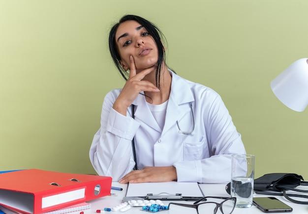 Selbstbewusste junge ärztin, die ein medizinisches gewand mit stethoskop trägt, sitzt am schreibtisch mit medizinischen instrumenten, die hand auf die wange legen, isoliert auf olivgrüner wand