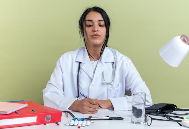 Selbstbewusste junge ärztin, die ein medizinisches gewand mit stethoskop trägt, sitzt am schreibtisch mit medizinischen werkzeugen, die etwas auf die zwischenablage schreiben, isoliert auf olivgrüner wand isolated