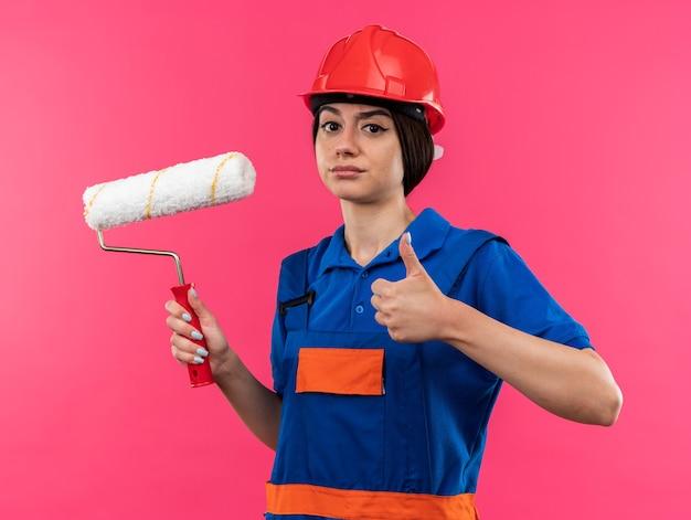 Selbstbewusste junge baumeisterin in uniform, die die walzenbürste hält, die daumen nach oben zeigt