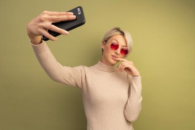 Selbstbewusste junge blonde frau mit sonnenbrille, die finger auf die lippe legt und selfie isoliert auf olivgrüner wand mit kopienraum macht