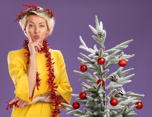 Selbstbewusste junge blonde frau mit weihnachtskopfkranz und lametta-girlande um den hals, die in der nähe des geschmückten weihnachtsbaums steht und die hand am kinn hält, mit geschürzten lippen isoliert auf lila wand
