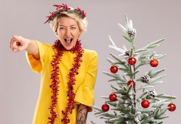 Selbstbewusste junge blonde frau mit weihnachtskopfkranz und lametta-girlande um den hals, die in der nähe des geschmückten weihnachtsbaums steht und gerade schreiend auf weiße wand zeigt