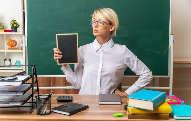 Selbstbewusste junge blonde lehrerin mit brille, die am schreibtisch mit schulmaterial im klassenzimmer sitzt und eine mini-tafel zeigt, die sie mit der hand auf der taille betrachtet