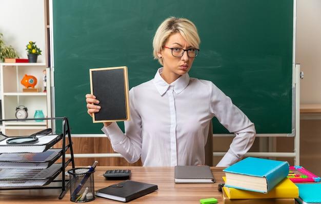 Selbstbewusste junge blonde lehrerin mit brille, die am schreibtisch mit schulwerkzeugen im klassenzimmer sitzt und eine mini-tafel zeigt, die die hand an der taille hält und in die kamera schaut