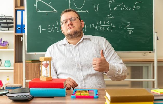 Selbstbewusste junge blonde lehrerin mit brille, die am schreibtisch mit schulwerkzeugen im klassenzimmer sitzt und in die kamera schaut, die den daumen nach oben zeigt