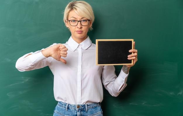 Selbstbewusste junge blonde lehrerin mit brille im klassenzimmer, die vor der tafel steht und eine mini-tafel zeigt, die nach vorne schaut und den daumen nach unten zeigt