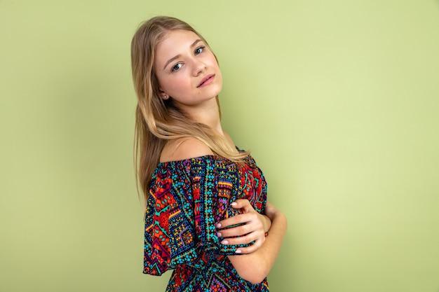Selbstbewusste junge blonde slawische frau, die seitlich steht und schaut