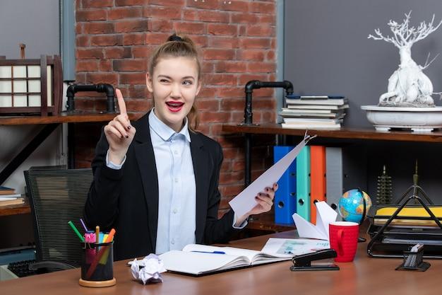 Selbstbewusste junge dame, die an einem tisch sitzt und das dokument im büro nach oben zeigt