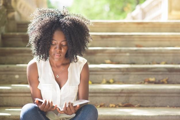 Selbstbewusste junge frau liest magazin auf treppen