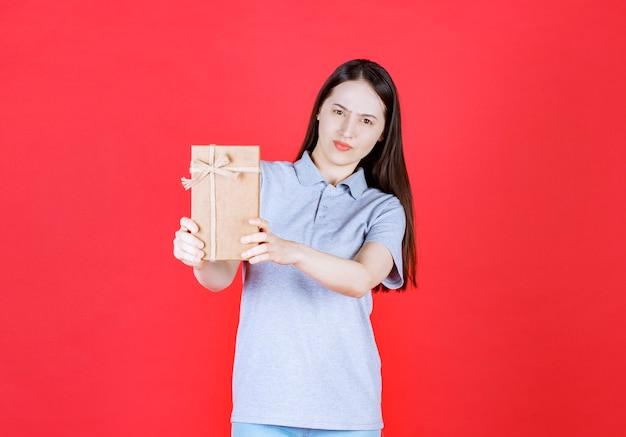 Selbstbewusste junge frau mit geschenkbox