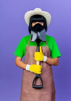 Selbstbewusste junge gärtnerin in uniform mit gartenhut und handschuhen hält und schaut über spaten