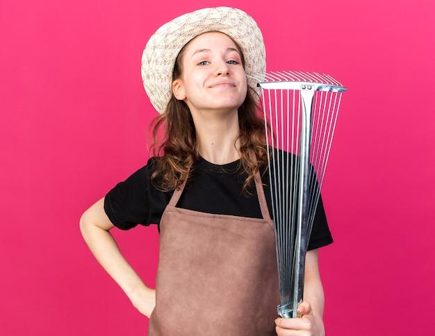 Selbstbewusste junge gärtnerin mit gartenhut, die blattrechen hält und hand auf die hüfte legt