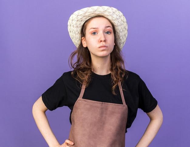 Selbstbewusste junge gärtnerin mit gartenhut, die die hände auf die hüften legt