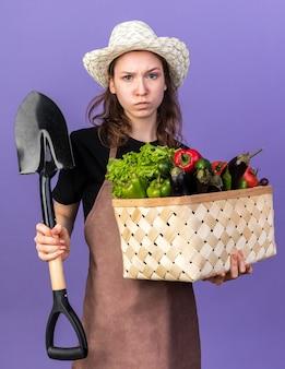 Selbstbewusste junge gärtnerin mit gartenhut, die gemüsekorb hält und spaten isoliert auf blauer wand hält