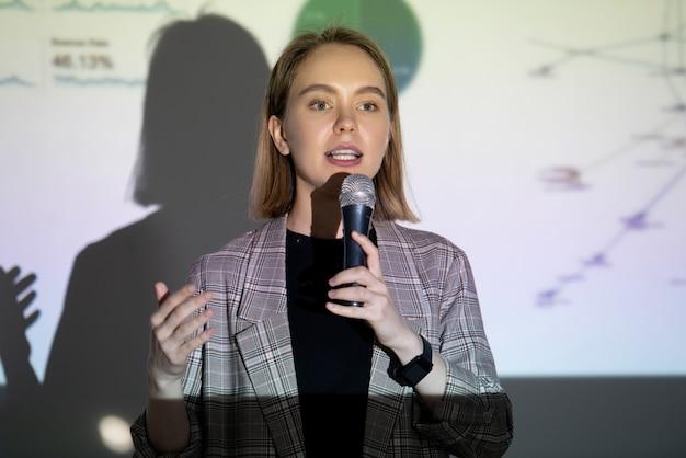 Selbstbewusste junge geschäftsfrau, die auf der entrepreneurship-konferenz über ihren erfolg im mikrofon spricht