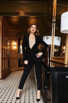 Selbstbewusste junge geschäftsfrau im schwarzen anzug posiert im vintage-interieur