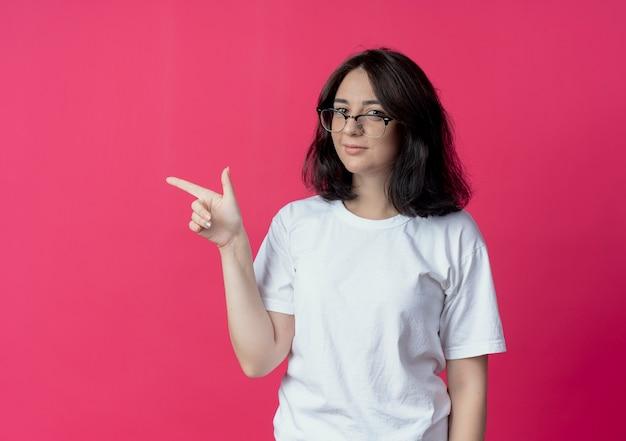 Selbstbewusste junge hübsche frau, die eine brille trägt, die zur seite auf purpurrote wand zeigt