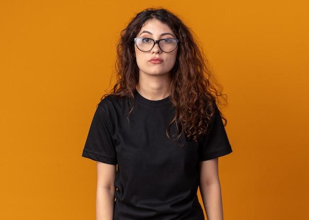 Selbstbewusste junge hübsche frau mit brille, die vorne isoliert auf orangefarbener wand mit kopierraum schaut
