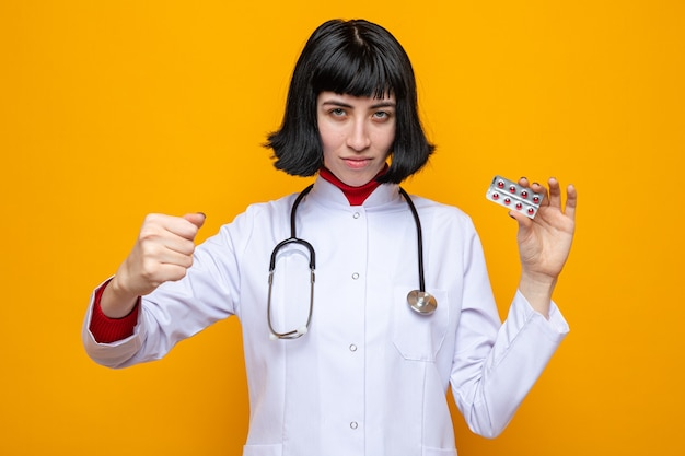 Selbstbewusste junge hübsche kaukasische frau in arztuniform mit stethoskop, die pillen hält und die faust hält