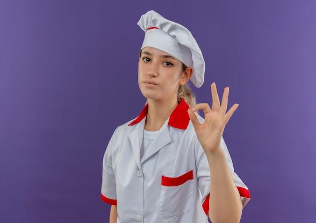 Selbstbewusste junge hübsche köchin in kochuniform, die ein gutes zeichen tut, das isoliert auf lila wand mit kopienraum aussieht?
