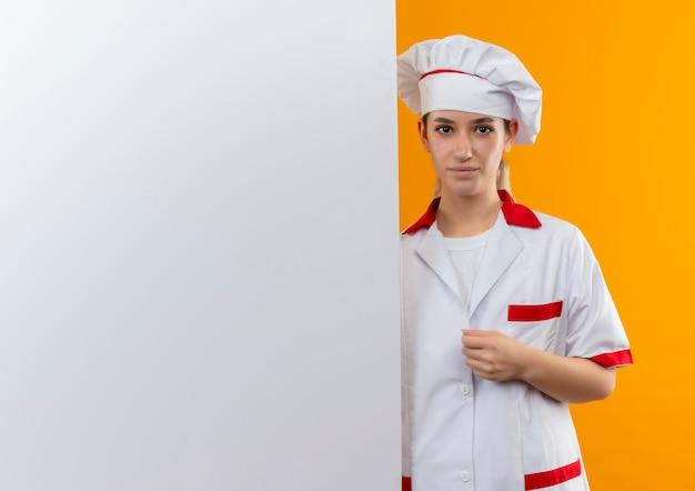 Selbstbewusste junge hübsche köchin in kochuniform, die hinter weißer wand steht und hand auf ihre uniform legt, isoliert auf oranger wand mit kopierraum
