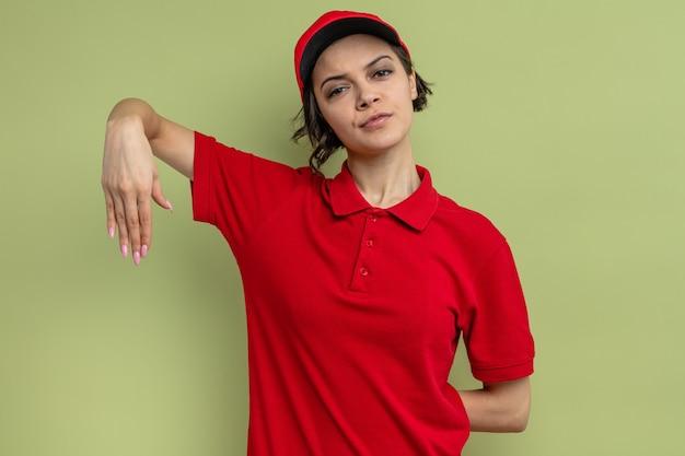Selbstbewusste junge hübsche lieferfrau, die die hand offen hält und nach vorne schaut