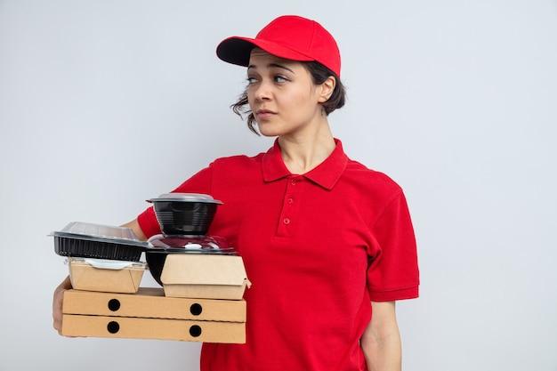 Selbstbewusste junge hübsche lieferfrau, die lebensmittelbehälter und verpackungen auf pizzakartons hält und auf die seite schaut