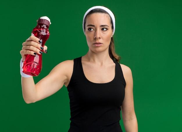 Selbstbewusste junge hübsche sportliche frau mit stirnband und armbändern, die eine wasserflasche ausstreckt und seitlich isoliert auf grüner wand mit kopierraum schaut