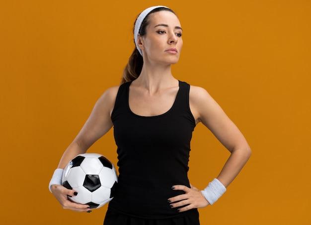 Selbstbewusste junge hübsche sportliche frau mit stirnband und armbändern, die fußball hält und die hand an der taille hält und auf die seite schaut