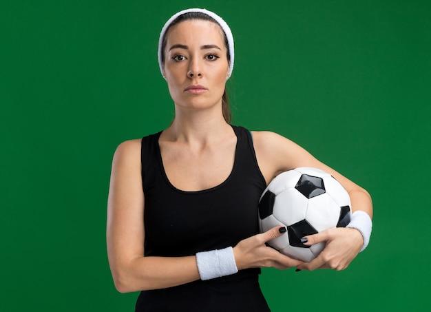 Selbstbewusste junge hübsche sportliche frau mit stirnband und armbändern, die fußball hält und nach vorne isoliert auf grüner wand mit kopienraum schaut