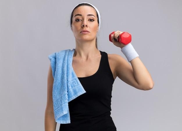 Selbstbewusste junge hübsche sportliche frau mit stirnband und armbändern, die hantel mit handtuch auf der schulter hält und nach vorne auf weiße wand mit kopienraum blickt