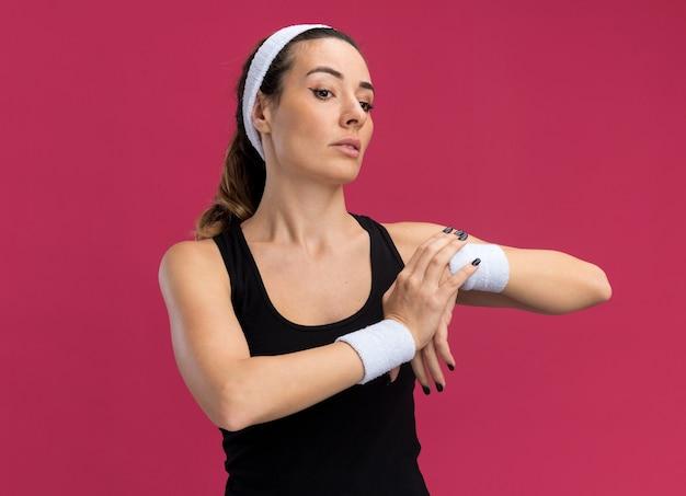 Selbstbewusste junge hübsche sportliche frau mit stirnband und armbändern, die nach unten schaut und die hand ausdehnt