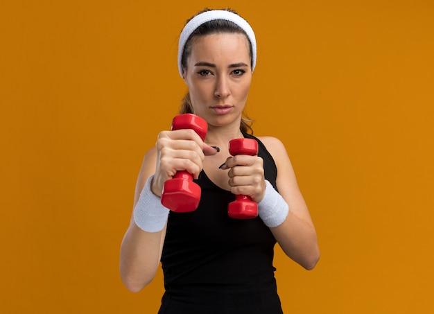 Selbstbewusste junge hübsche sportliche frau mit stirnband und armbändern mit hanteln und boxgeste