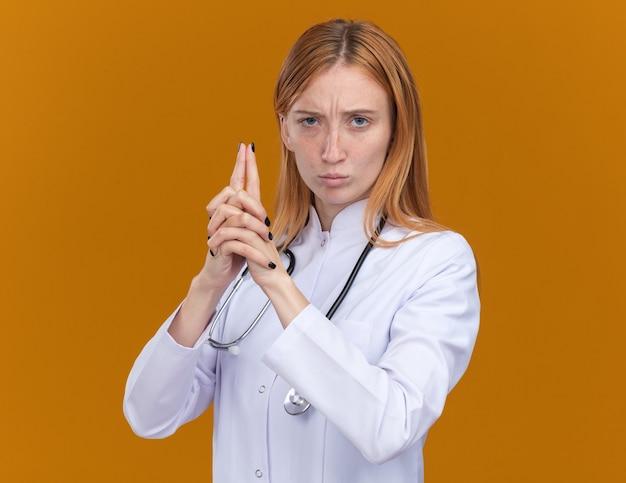 Selbstbewusste junge ingwerärztin, die medizinische robe und stethoskop trägt und nach vorne schaut, die pistolengeste isoliert auf oranger wand