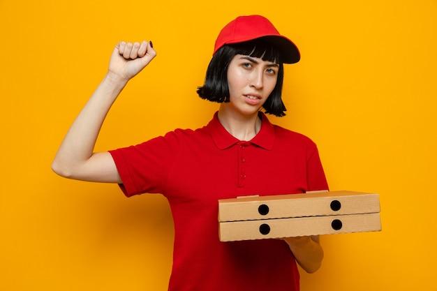Selbstbewusste junge kaukasische lieferfrau, die pizzakartons hält und ihre faust hochhebt