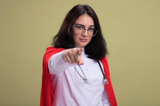 Selbstbewusste junge kaukasische superheldin in rotem umhang mit arztuniform und stethoskop mit brille, die nach vorne schaut und zeigt