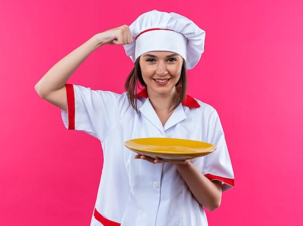 Selbstbewusste junge köchin, die eine kochuniform trägt und eine platte mit starker geste zeigt, die auf rosa wand isoliert ist?