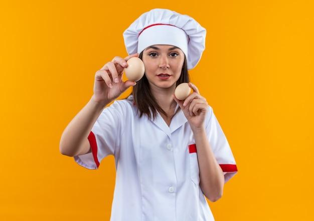 Selbstbewusste junge köchin in kochuniform, die eier in die kamera hält, isoliert auf orangefarbenem hintergrund