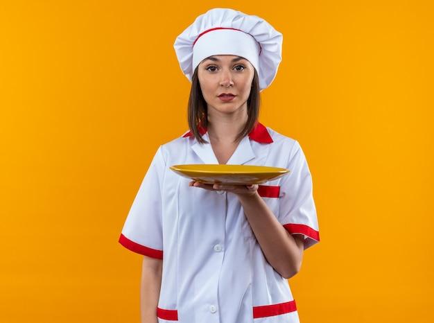 Selbstbewusste junge köchin in kochuniform mit teller isoliert auf orangem hintergrund