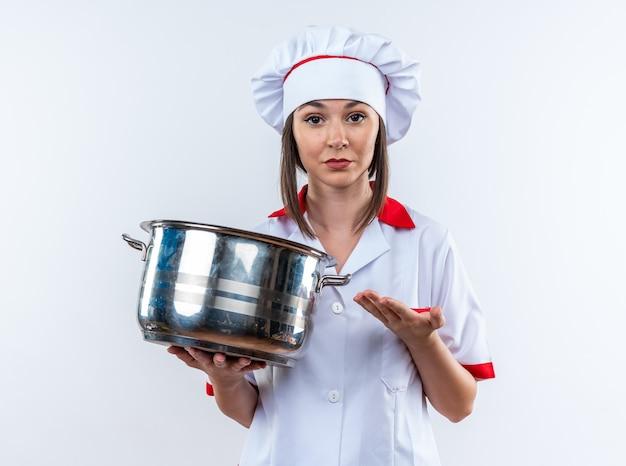Selbstbewusste junge köchin mit kochuniform, die auf eine weiße wand isoliert und auf den topf zeigt