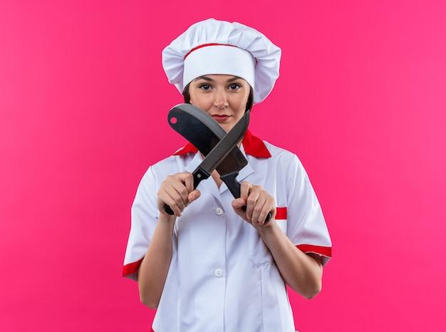 Selbstbewusste junge köchin mit kochuniform schärfen das messer einzeln auf rosa hintergrund on