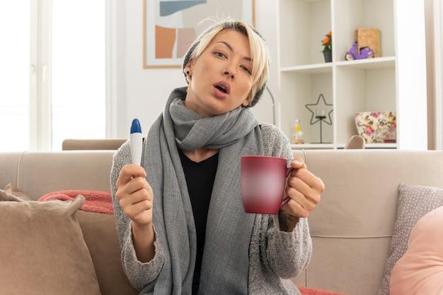 Selbstbewusste junge kranke slawische frau mit schal um den hals mit wintermütze mit thermometer und tasse auf der couch im wohnzimmer sitzend