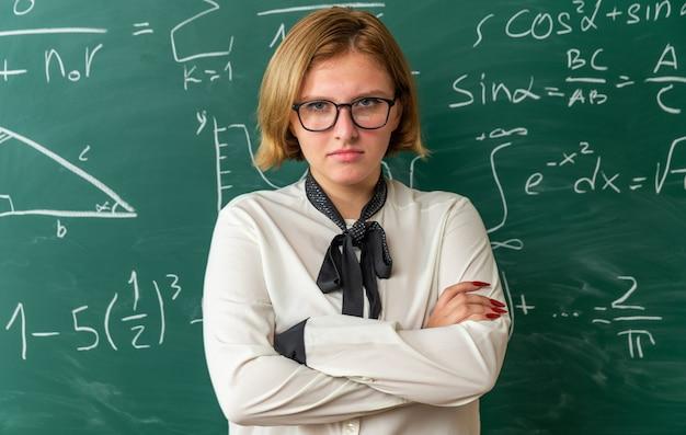 Selbstbewusste junge lehrerin mit brille, die vor der tafel steht und die hände im klassenzimmer kreuzt