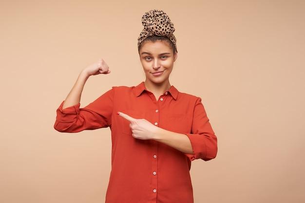 Selbstbewusste junge reizende brünette frau mit natürlichem make-up, das mit zeigefinger auf ihrem bizeps zeigt, während sie anmaßend nach vorne schaut und über beige wand aufwirft